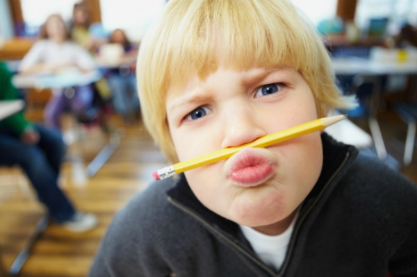 Funny young school student balancing a pencil on his nose